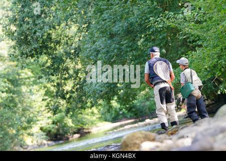 Vue arrière de père et fils la voler-pêche en rivière Banque D'Images