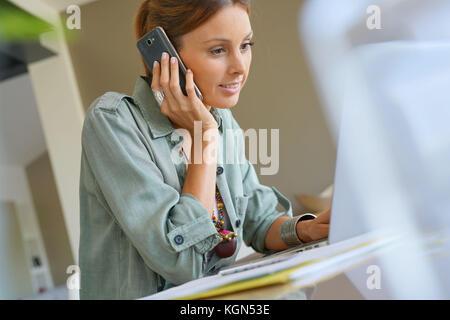 Femme travail à domicile sur ordinateur portable et parlant au téléphone Banque D'Images