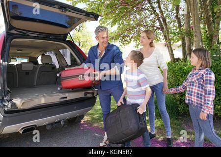 Happy Family charger des bagages dans le véhicule Banque D'Images