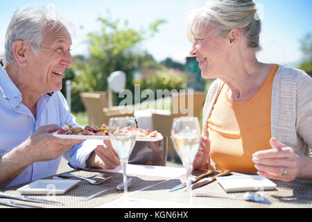 Senior couple enjoying repas au restaurant en plein air Banque D'Images