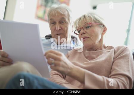 Senior couple in canapé la lecture des documents officiels Banque D'Images
