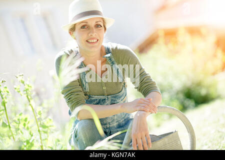 Blonde woman with hat le jardinage sur sunny day Banque D'Images