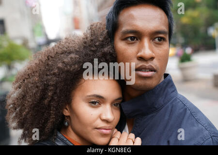 Ethnic couple walking in new york city street sur jour de pluie