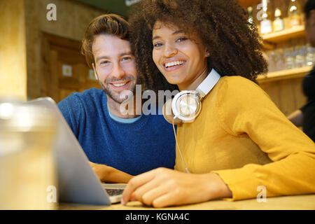 Couple in restaurant branché sur Internet avec ordinateur portable Banque D'Images