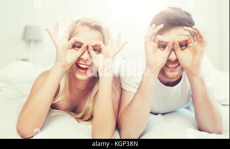 Heureux couple lying in bed at home Banque D'Images