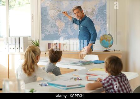 Teacher standing in classroom, pour les enfants fréquentant la leçon de géographie Banque D'Images