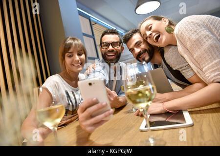 Groupe d'amis en prenant des photos en selfies bar Banque D'Images