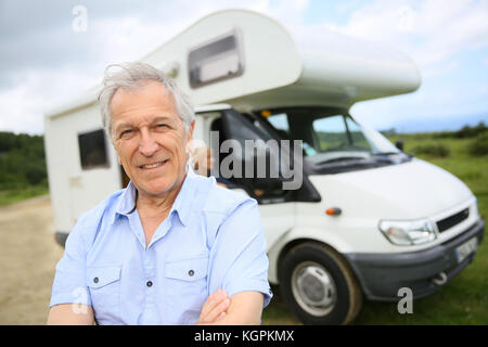 Portrait of happy senior man standing in front of camping Banque D'Images