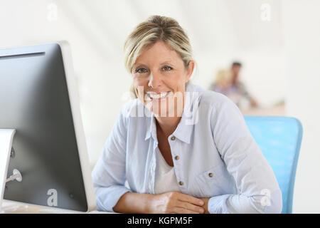 Mature businesswoman sitting in front of desktop Banque D'Images