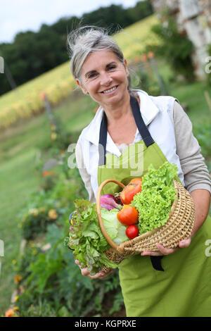 Senior woman holding basket of fresh vegetables Banque D'Images