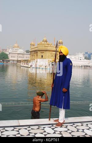 Un garde Sikh avec un homme derrière le sacré dans le bain l'Amrit Sarovar Lake, en face du Golden Temple, Amritsar, Banque D'Images
