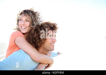 Man giving piggyback ride pour petite amie sur la plage Banque D'Images