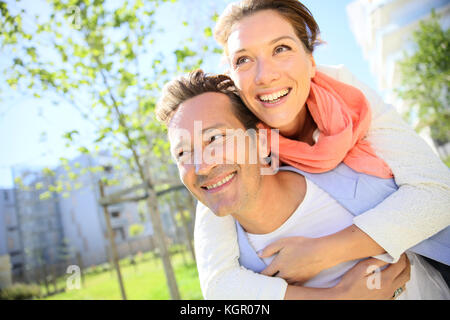 Man giving piggyback ride to woman in park Banque D'Images
