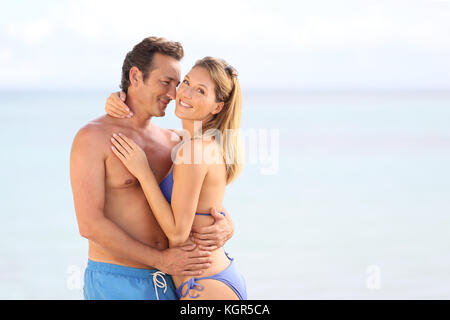 Couple aimant en maillot embrassant sur la plage Banque D'Images