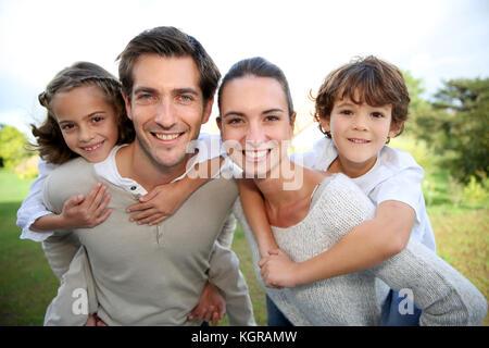 Les parents qui piggyback ride aux enfants Banque D'Images