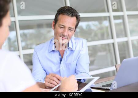 Gros plan du businessman having contrat signature de client sur tablette Banque D'Images