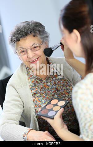 Accueil aide soignant femme âgée de mettre du maquillage sur Banque D'Images