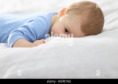 8-month-old baby boy laying on bed Banque D'Images