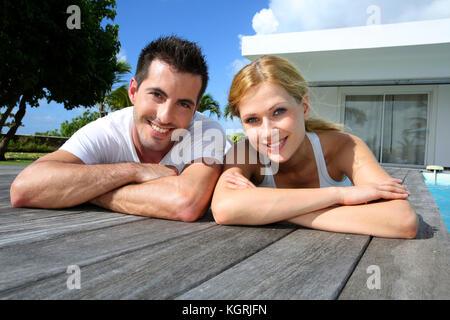 Couple sur la terrasse de la piscine après l'entraînement Banque D'Images