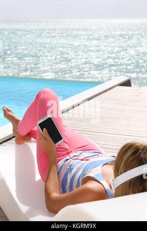Woman relaxing in chaise longue avec écouteurs Banque D'Images