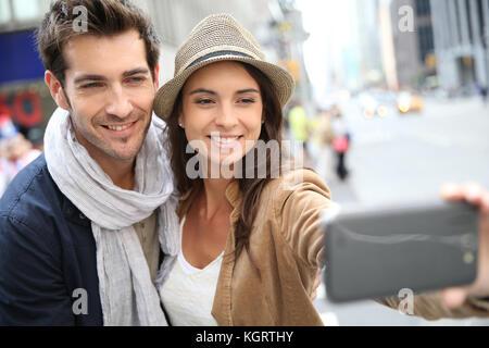 Couple dans Manhattan prenant photo with smartphone Banque D'Images
