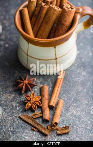 Les bâtons de cannelle et l'étoile d'anis sur la vieille table de cuisine. Banque D'Images