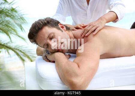 Bel homme allongé sur un lit de massage Banque D'Images