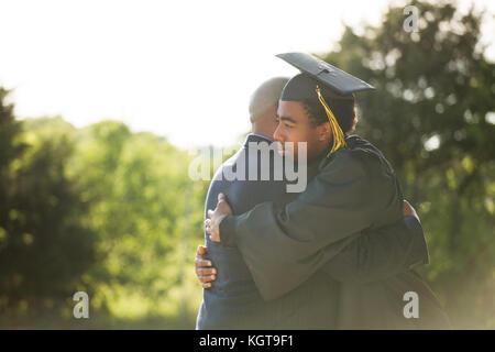 Père serrant son fils à son diplôme.