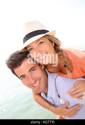 Man giving piggyback ride de belle fille blonde avec chapeau Banque D'Images