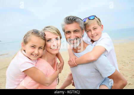 Les parents qui piggyback ride pour les enfants à la plage Banque D'Images