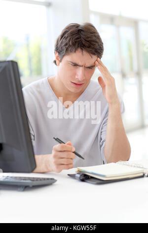 Portrait of office worker ayant un mal de tête au travail Banque D'Images