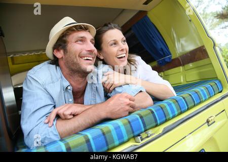 Cheerful young couple portant sur un camping-car Banque D'Images