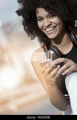 Fitness petite fille en utilisant smartphone et casque sur le jogging jour Banque D'Images