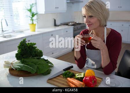Belle femme ayant thé citron à table dans la cuisine Banque D'Images