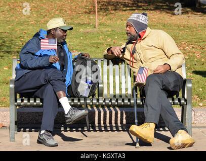 Anciens combattants non identifiés ayant une conversation tout en maintenant des drapeaux américains sur la Journée Banque D'Images