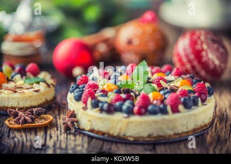 Cheescake aux fruits frais Fruits rouges Fraises Framboises et anis étoilé. cheescake de noël avec décoration de Banque D'Images