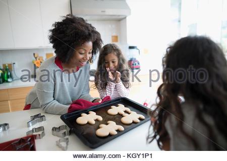 Mère et filles baking christmas gingerbread cookies in kitchen Banque D'Images