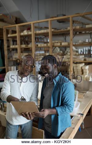 Entreprise familiale père et fils à la recherche d'entrepreneurs à presse-papiers en atelier Banque D'Images