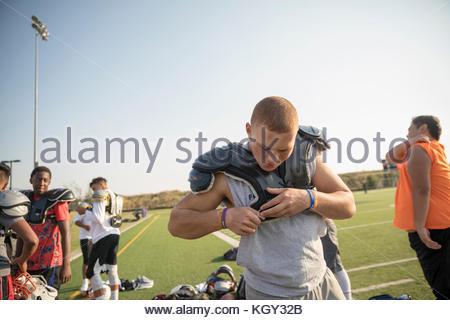Teenage boy high school football player putting on padding pour la pratique par beau terrain de football Banque D'Images