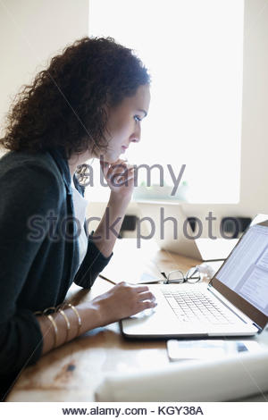Les femmes ciblées architect working at laptop in office Banque D'Images