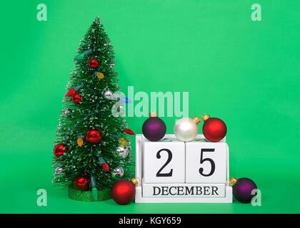 Des cales de bois montrant date 25 décembre, noël, assis sur un fond vert avec petit arbre de Noël décoré à côté, Banque D'Images