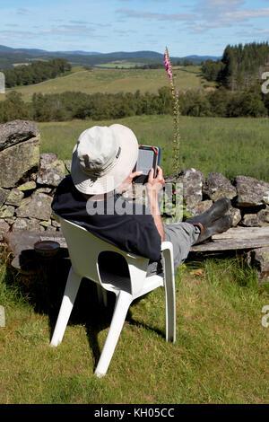 Un homme à la retraite en vacances de détente et la lecture d'un livre sur un Amazon Kindle Banque D'Images