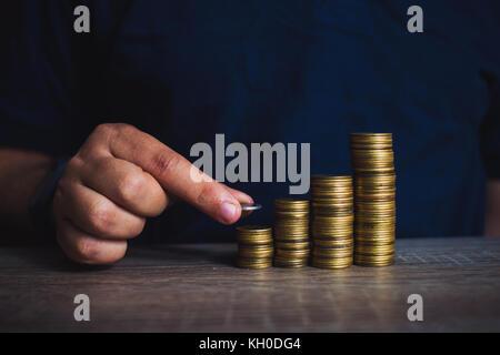 La main de l'homme mettre de l'argent monnaie pour pile de pièces. l'argent, financier, la croissance de l'entreprise Banque D'Images