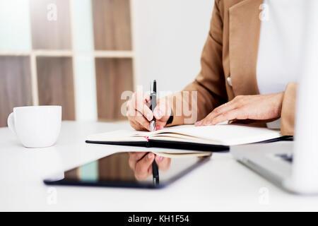 Mains de femmes d'affaires financières manager prendre des notes lorsque vous travaillez sur le rapport Banque D'Images