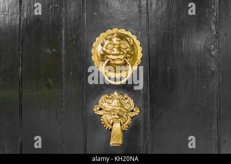 Or ou laiton heurtoir de porte ouvragée sur noir Banque D'Images
