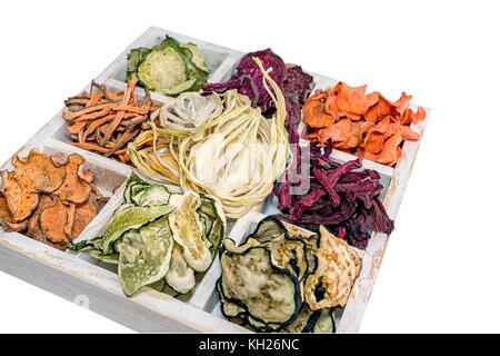 Des jetons colorés de différents légumes frais dans une boîte en bois blanc sur un fond blanc. Isolées. La structure Banque D'Images