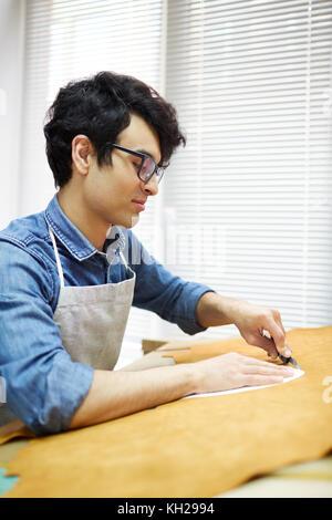 Maître d'artisanat se coupe petit morceau de cuir beige à partir de la plus grande Banque D'Images