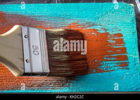 Badigeonner avec de la peinture à la main. un homme bleu peint sur un pinceau marron Banque D'Images