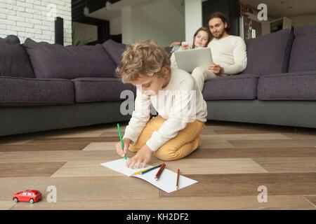 Garçon d'âge préscolaire fils dessin avec crayons de couleur dans l'album alors que les parents à l'aide de l'ordinateur Banque D'Images