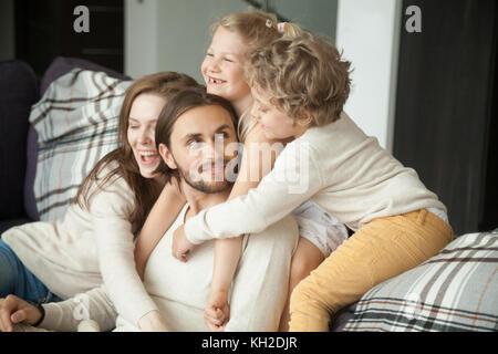 Heureux parents et petits enfants rire s'amuser assis sur un canapé, pour les enfants et femme serrant mari papa Banque D'Images